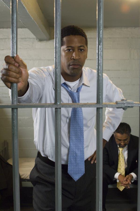 Hombre de negocios In Prison Cell imagenes de archivo