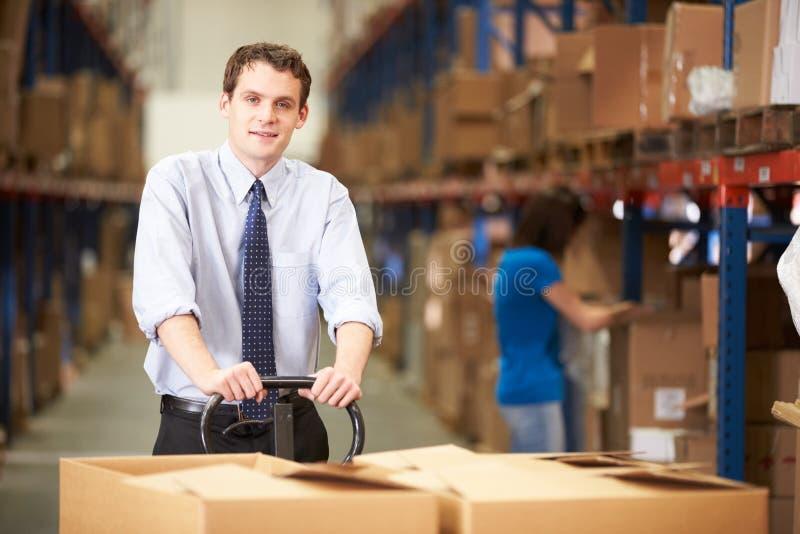 Hombre de negocios Pulling Pallet In Warehouse fotos de archivo libres de regalías
