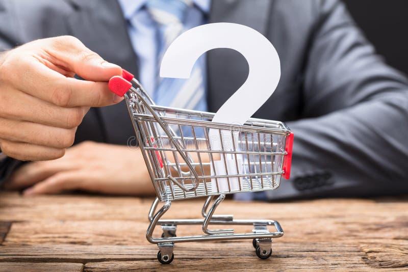 Hombre de negocios Pushing Question Mark In Shopping Cart fotografía de archivo