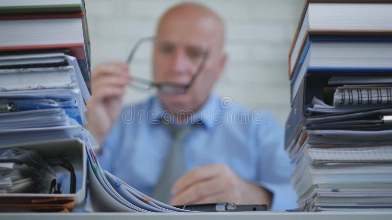 Hombre de negocios Put His Eyeglasses de la imagen borrosa y comienzo que trabaja en sitio del archivo imagenes de archivo