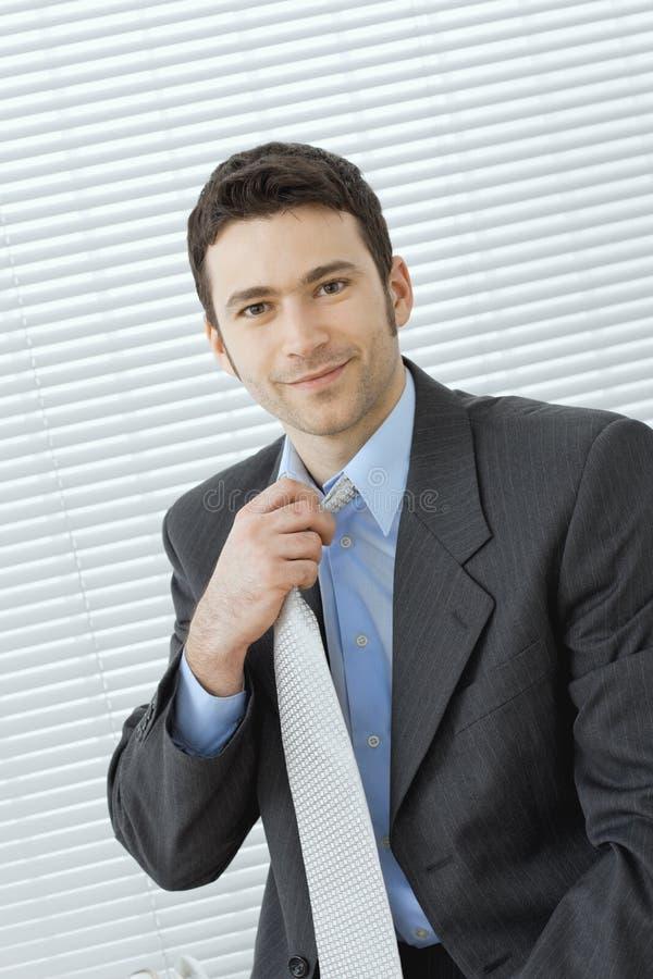 Hombre de negocios que ajusta el lazo imagen de archivo