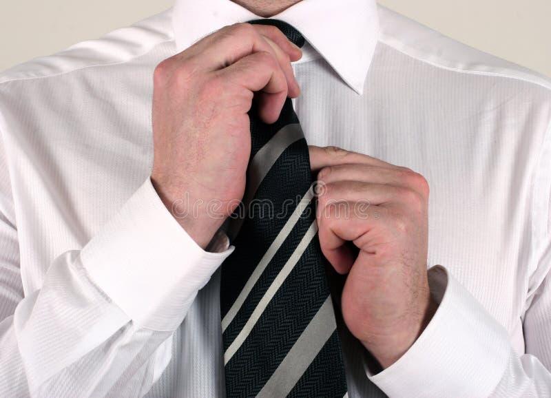 Hombre de negocios que ajusta el lazo fotos de archivo