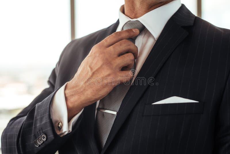 Hombre de negocios que ajusta su corbata fotos de archivo