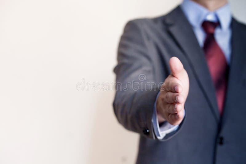 Hombre de negocios que alcanza hacia fuera la mano a la sacudida - concepto del negocio y G imagen de archivo