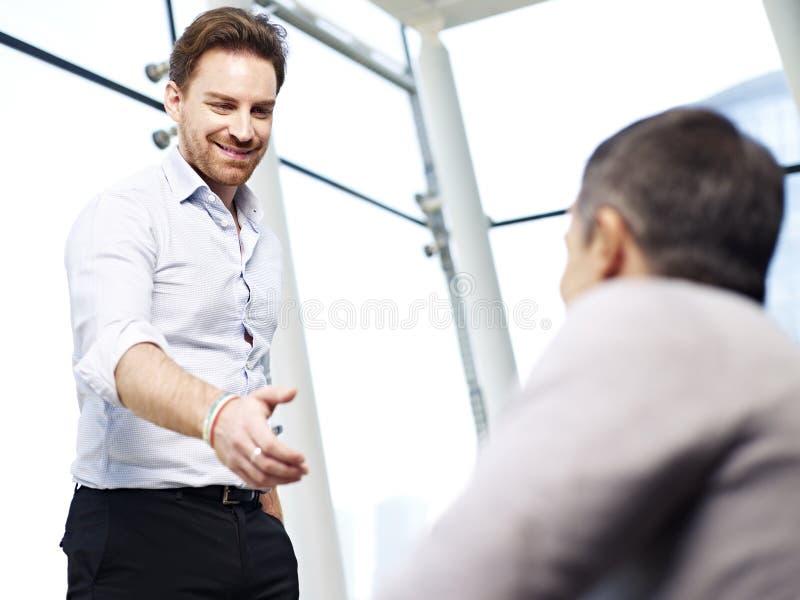 Hombre de negocios que alcanza hacia fuera para un apretón de manos imagenes de archivo