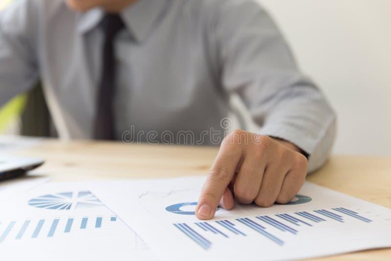 Hombre de negocios que analiza cartas y gráficos con compu moderno del ordenador portátil foto de archivo