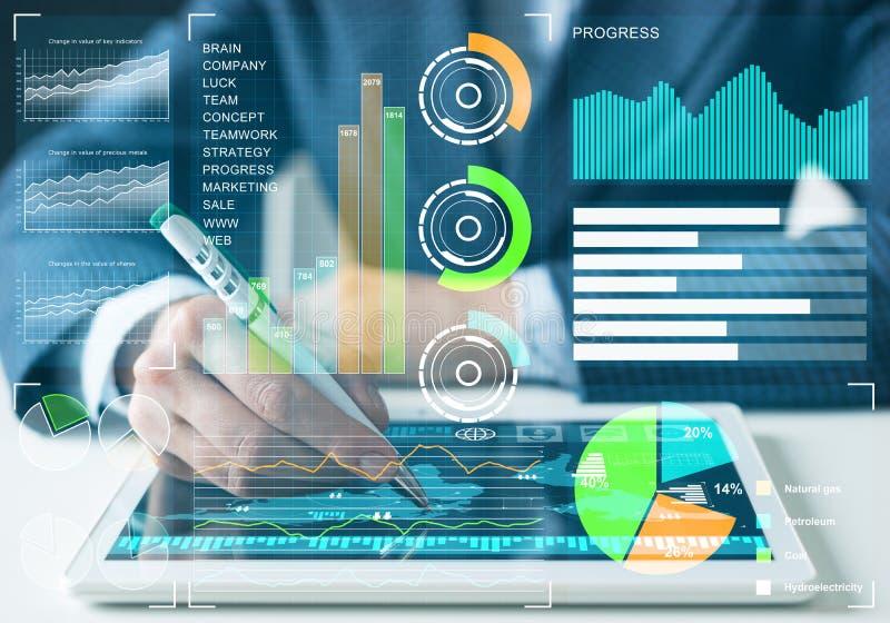 Hombre de negocios que analiza datos financieros en la tableta imagen de archivo libre de regalías