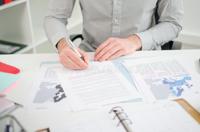 Hombre de negocios que analiza documentos económicos fotografía de archivo libre de regalías