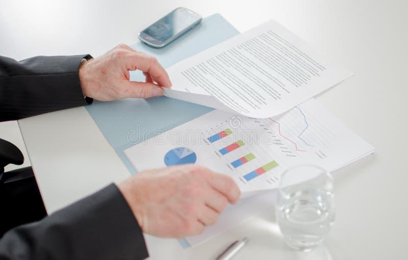 Hombre de negocios que analiza documentos económicos imagen de archivo