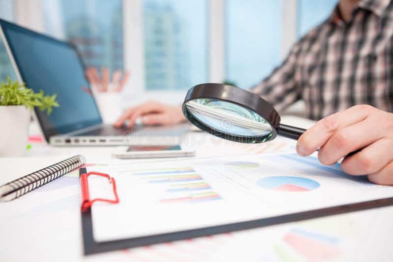 Hombre de negocios que analiza gráficos de negocio con la lupa imagenes de archivo