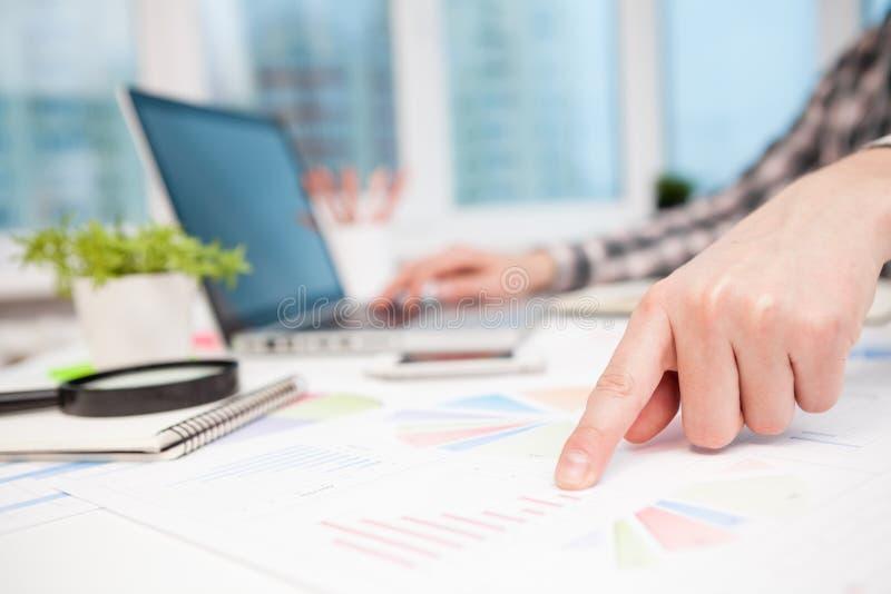 Hombre de negocios que analiza gráficos y diagramas en la tabla de madera fotografía de archivo libre de regalías