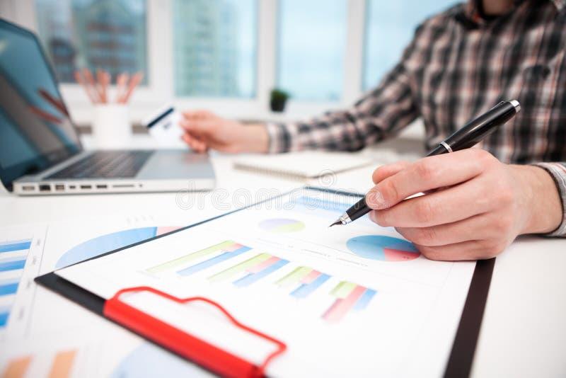 Hombre de negocios que analiza gr?ficos y diagramas en la tabla de madera foto de archivo libre de regalías
