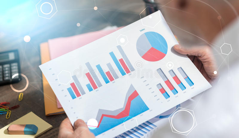 Hombre de negocios que analiza los datos financieros, exposición doble, efecto luminoso foto de archivo libre de regalías