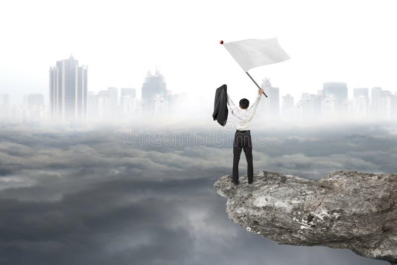 Hombre de negocios que anima en bandera que agita del acantilado con paisaje urbano nublado fotos de archivo