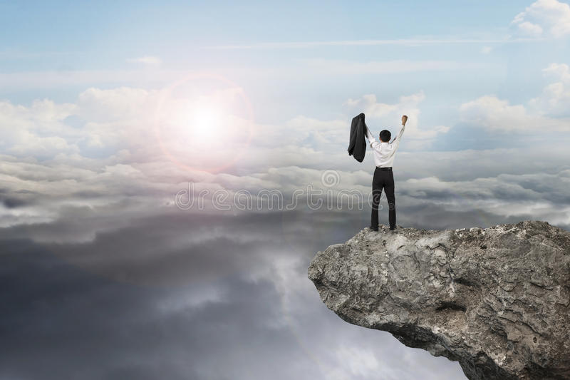 Hombre de negocios que anima en el acantilado con cloudsca natural de la luz del día del cielo foto de archivo libre de regalías