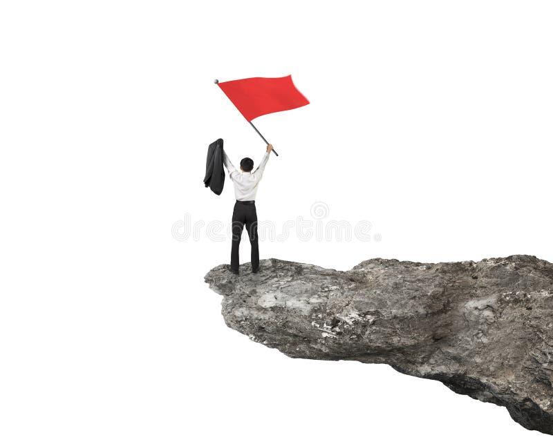 Hombre de negocios que anima y que agita la bandera roja encima del acantilado imagen de archivo