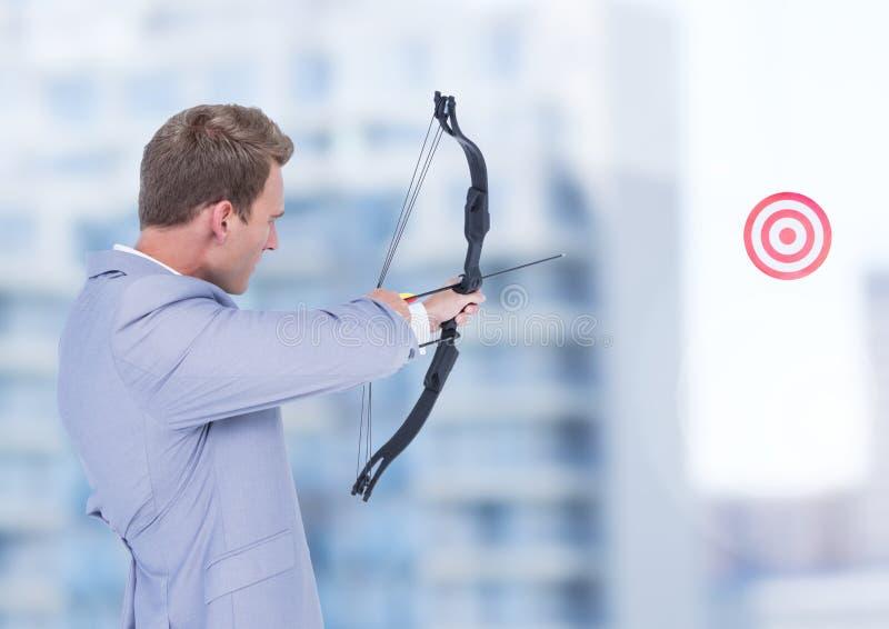 Hombre de negocios que apunta el arco y la flecha a la blanco foto de archivo libre de regalías