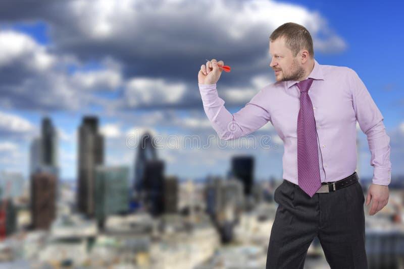 Hombre de negocios que apunta por el dardo con la ciudad moderna adentro imagen de archivo