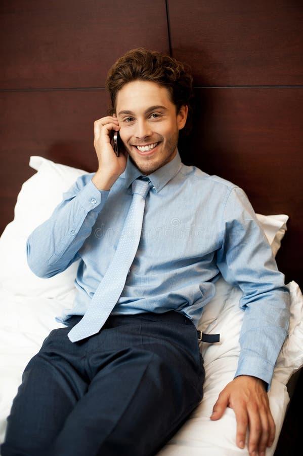 Hombre de negocios que atiende a llamadas personales después de trabajo imagen de archivo libre de regalías