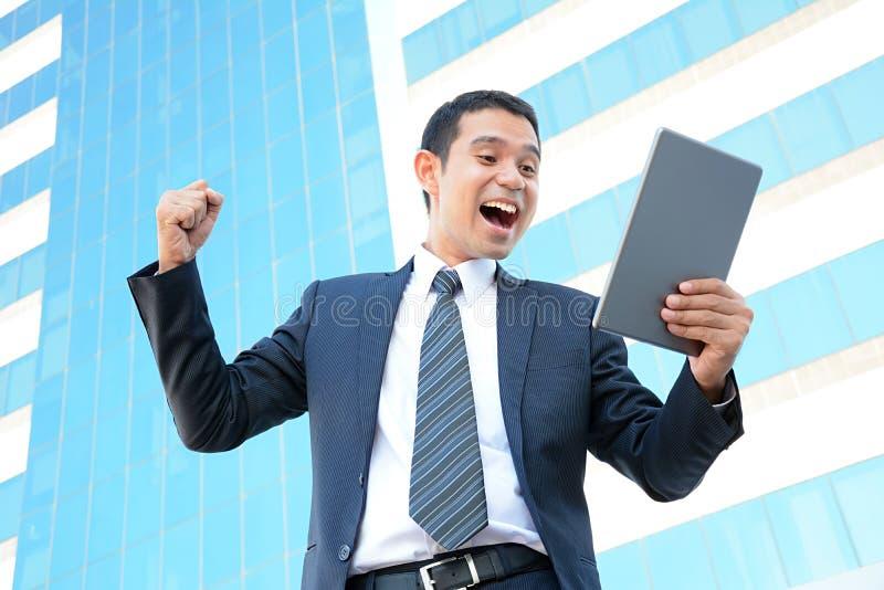 Hombre de negocios que aumenta su brazo mientras que mira la tableta fotos de archivo