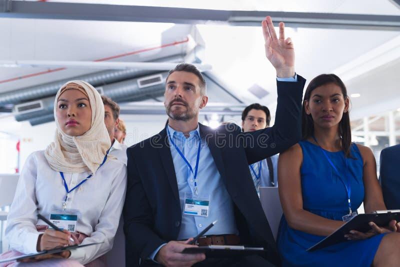 Hombre de negocios que aumenta su mano mientras que asiste a seminario del negocio imagenes de archivo