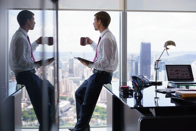 Hombre de negocios que bebe Coffe y que lee noticias en la tableta imagen de archivo