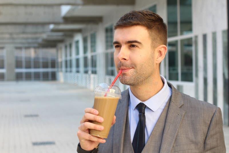 Hombre de negocios que bebe un café de hielo imagen de archivo