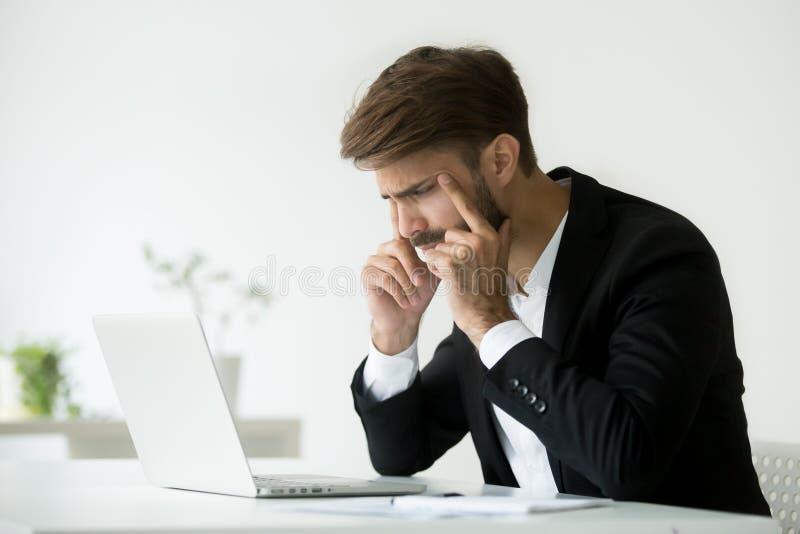 Hombre de negocios que bizquea los ojos que intentan enfocar la mirada del SCR del ordenador portátil imagen de archivo libre de regalías