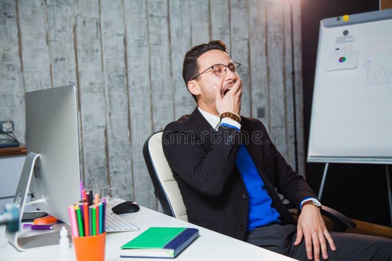 Hombre de negocios que bosteza en el concepto de trabajo aburrido de la oficina imagen de archivo libre de regalías