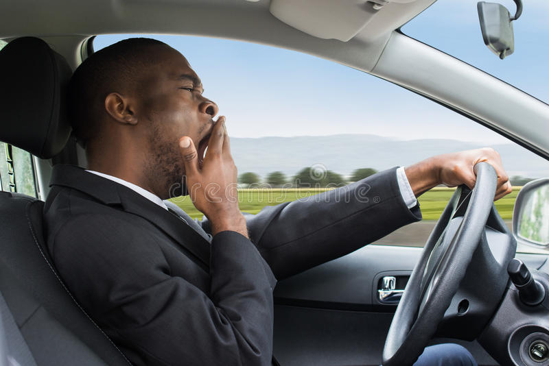 Hombre de negocios que bosteza mientras que conduce el coche imagenes de archivo