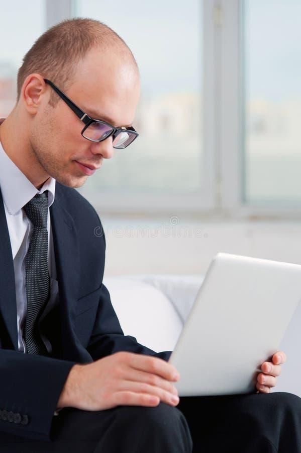 Hombre de negocios que busca con el ordenador portátil en Internet imagen de archivo
