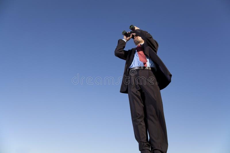 Hombre de negocios que busca con sus prismáticos imagen de archivo