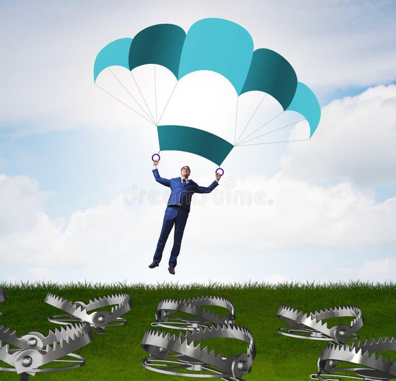 Hombre de negocios que cae en trampa en el paraca?das fotografía de archivo