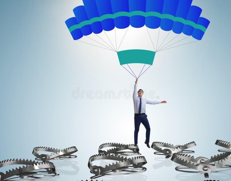 Hombre de negocios que cae en trampa en el paraca?das foto de archivo