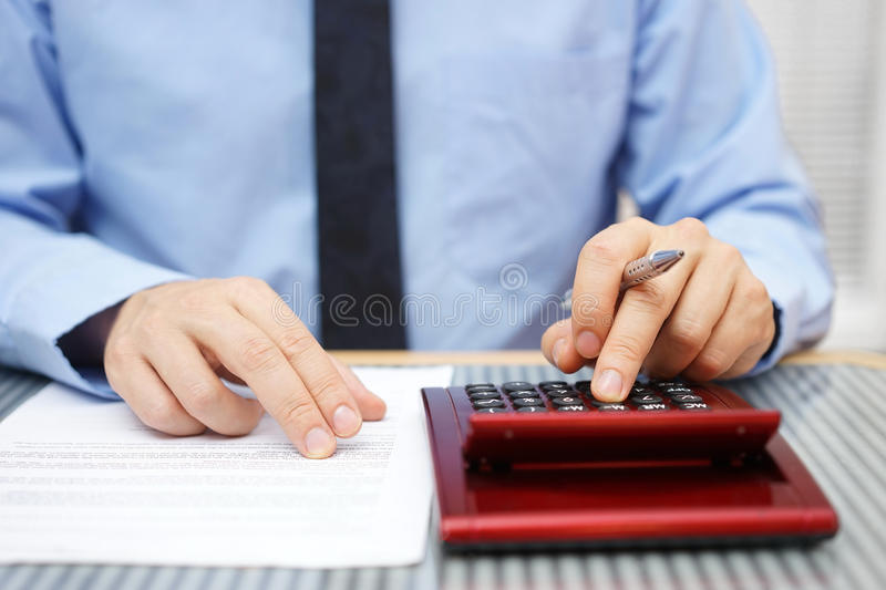 Hombre de negocios que calcula y que comprueba los artículos del acuerdo imagen de archivo