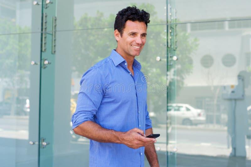 Hombre de negocios que camina afuera con el teléfono celular foto de archivo