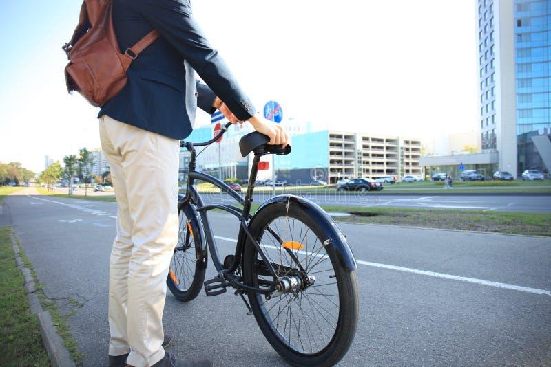Hombre de negocios que camina con la bici en calle después de trabajo imágenes de archivo libres de regalías
