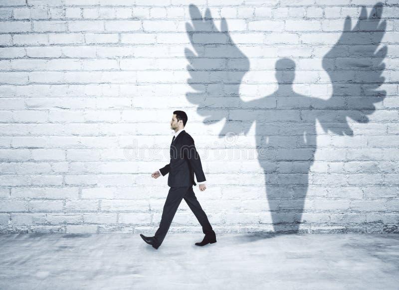 Hombre de negocios que camina con la sombra del ángel imagen de archivo