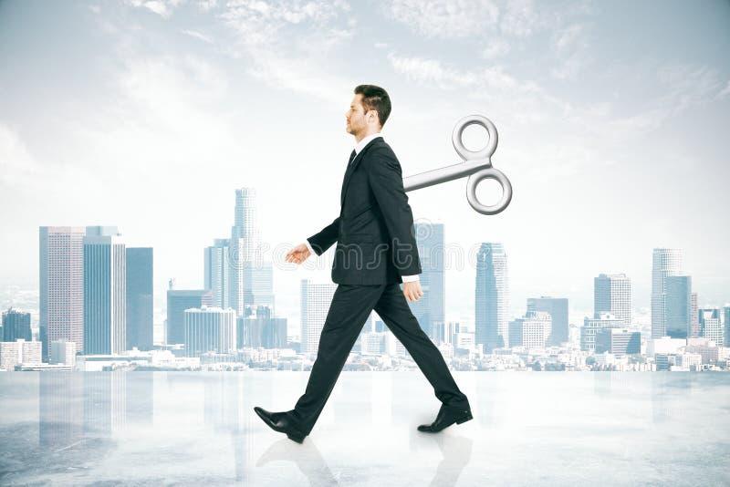 Hombre de negocios que camina con llave de la conclusión fotografía de archivo
