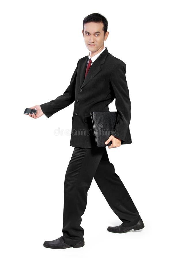 Hombre de negocios que camina de lado imagen de archivo