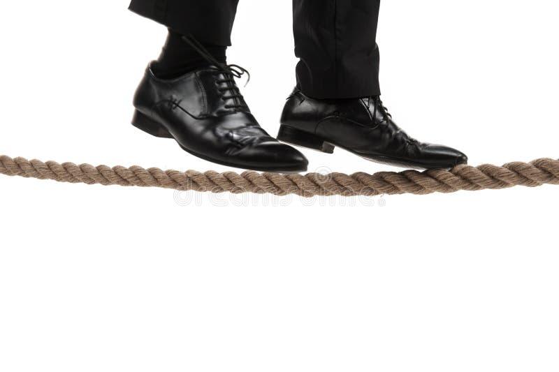 Hombre de negocios que camina en cuerda tirante en el fondo blanco foto de archivo libre de regalías