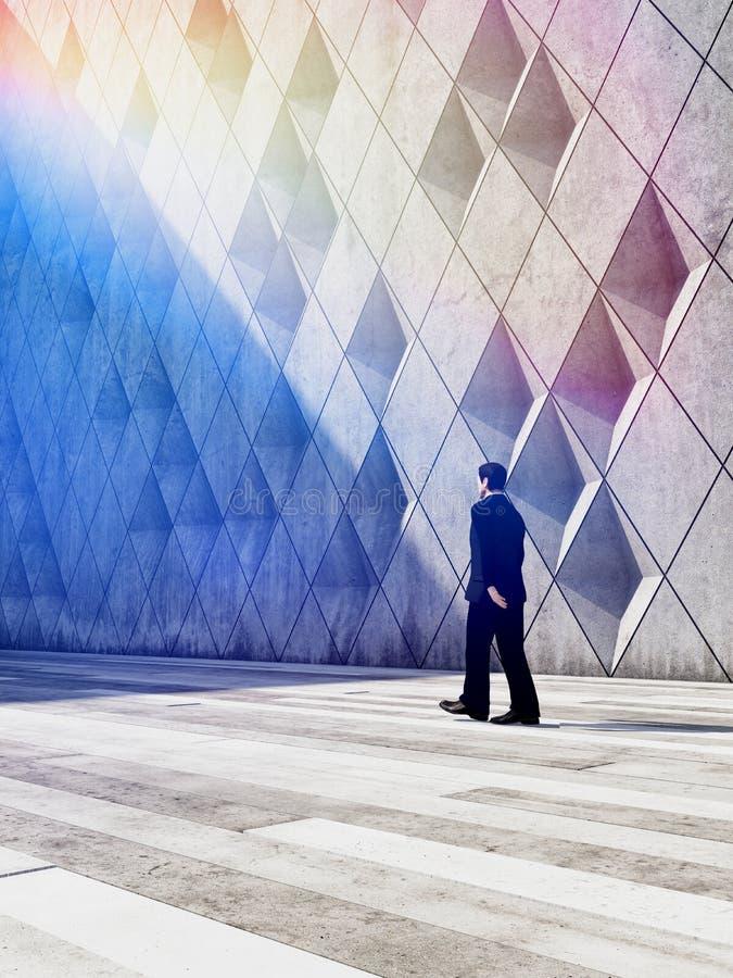 Hombre de negocios que camina en edificios del diseño arquitectónico fotos de archivo