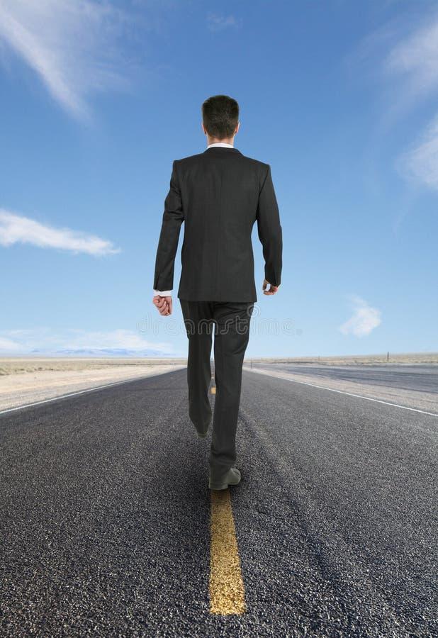 Hombre de negocios que camina en el camino imagenes de archivo