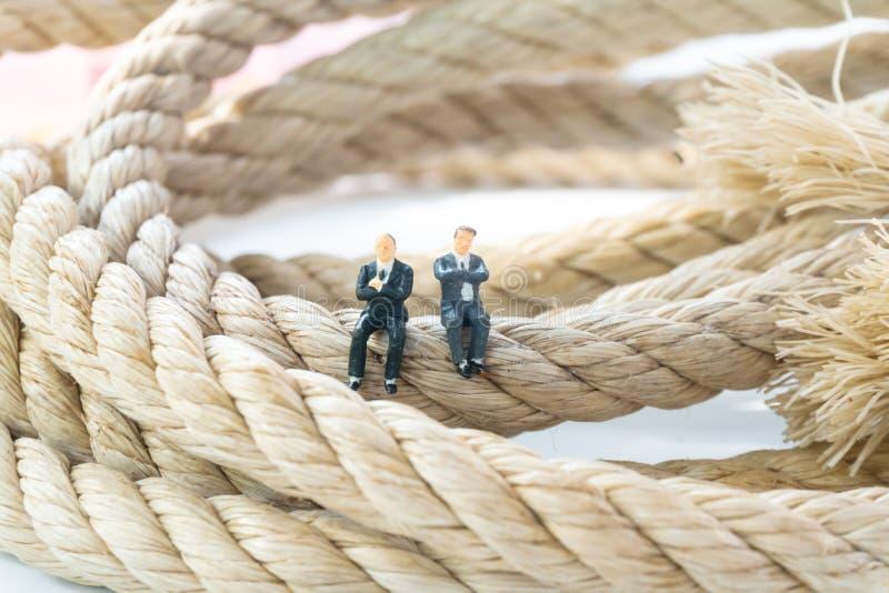 Hombre de negocios que camina en el cierre largo de la cuerda para arriba foto de archivo