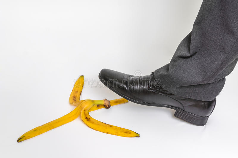 Hombre de negocios que camina en la cáscara del plátano - concepto del riesgo de negocio imagen de archivo libre de regalías