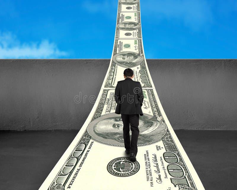 Hombre de negocios que camina en manera del dinero sobre el muro de cemento fotos de archivo libres de regalías