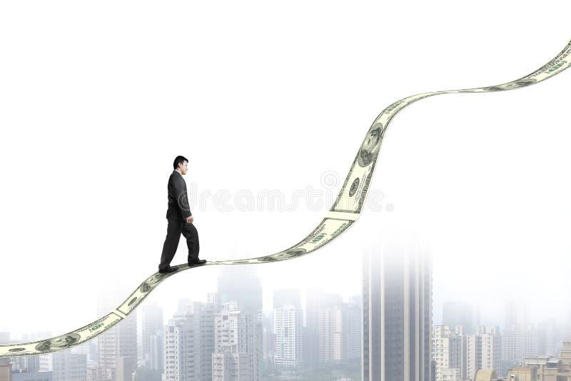 Hombre de negocios que camina en tendencia cada vez mayor del dinero con la opinión de la ciudad fotos de archivo