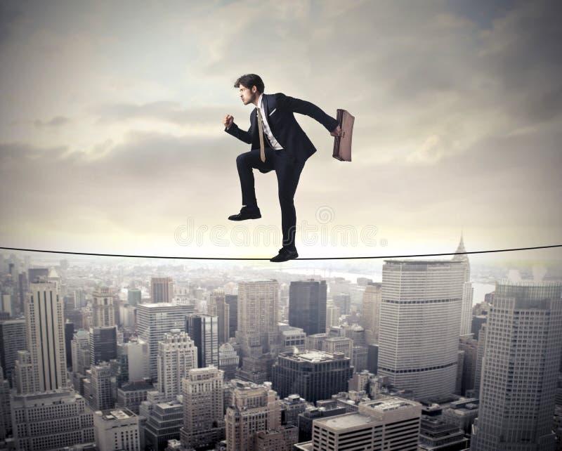 Hombre de negocios que camina en una cuerda foto de archivo