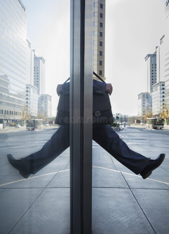 Hombre de negocios que camina hacia fuera en la calle, reflexión en el vidrio del edificio foto de archivo