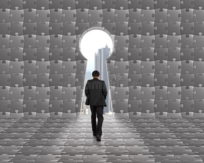 Hombre de negocios que camina hacia la puerta dominante de la forma con el backgroun de los rompecabezas fotografía de archivo libre de regalías